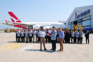 Employees of Korean Air and Qantas Airways pose together after Korean Air completed its first repaint of a Qantas A380 on May 24, at Korean Air's painting facility at Gimhae International Airport.