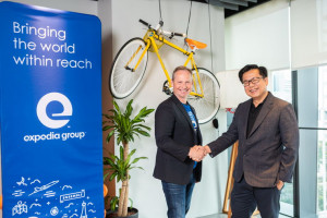 Mark Okerstrom, President and CEO, Expedia Group (left) sealing the 100 Experiments partnership with Laurence Liew, Director, AI Industry Innovation, AI Singapore (right)